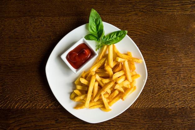 Pommes-frites mit soße auf einer weißen platte Premium Fotos