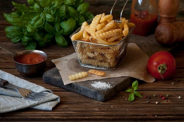 Pommes-friteskartoffeln, tomatenketschup und senf auf rustikalem hölzernem hintergrund. Premium Fotos