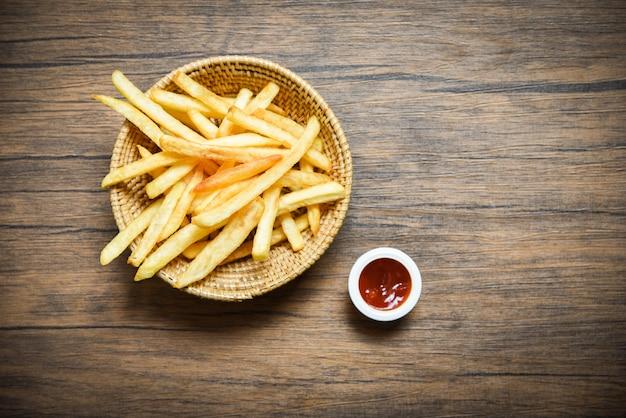 Pommes-friteskorb und -ketschup auf hölzernem speisetischhintergrund Premium Fotos