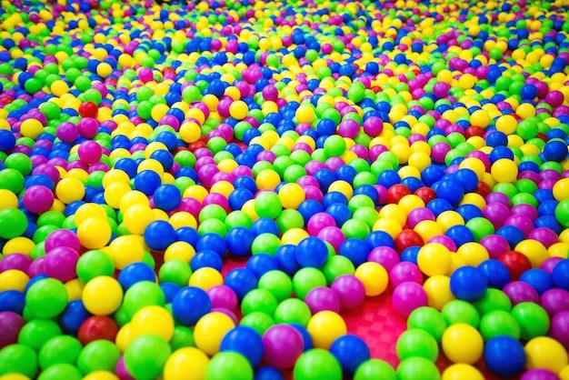 Pool mit plastikkugeln aus grün, blau, rosa, rot und gelb. Premium Fotos