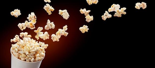 Popcorn fliegt aus pappkarton. auf schwarzem hintergrund isoliert Premium Fotos
