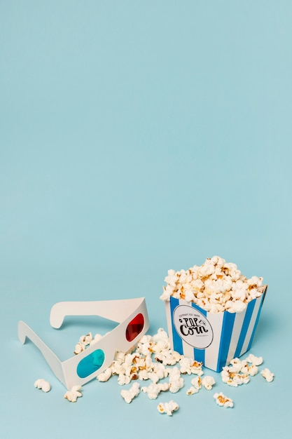 Popcorn füllte den kasten mit gläsern 3d gegen blauen hintergrund aus Kostenlose Fotos