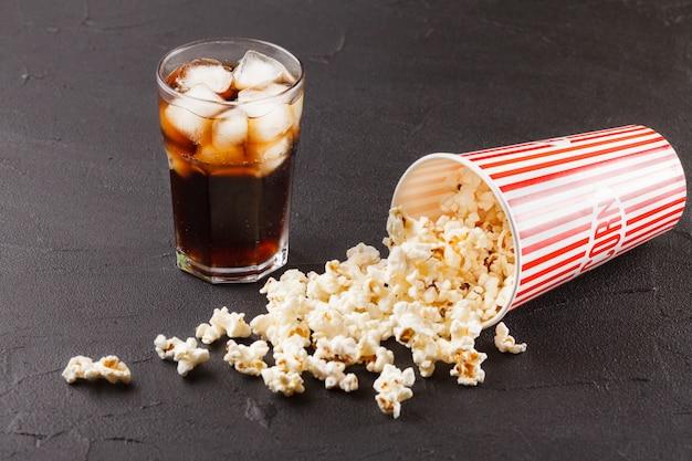 Popcorn horizontale banner. rot entfernte papierschale, kerne, die auf dunklem hintergrund liegen. Premium Fotos