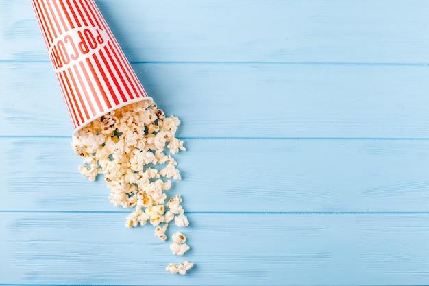 Popcorn horizontale banner. rot entfernte papierschale und kerne, die auf blauem hölzernem hintergrund liegen. Premium Fotos