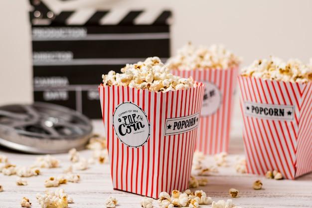 Popcorn im drei gestreiften eimer mit filmrolle und filmklappe auf hölzernem brett Kostenlose Fotos
