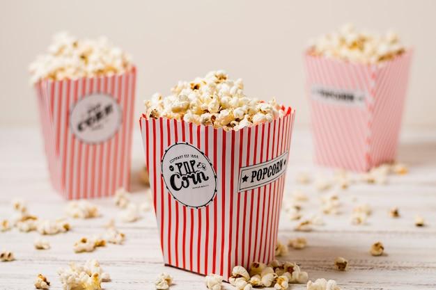 Popcorn im drei roten und weißen popcornkasten auf holztisch Kostenlose Fotos