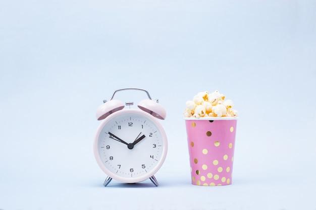 Popcorn in einem hellen glas und in einem wecker auf blau Premium Fotos
