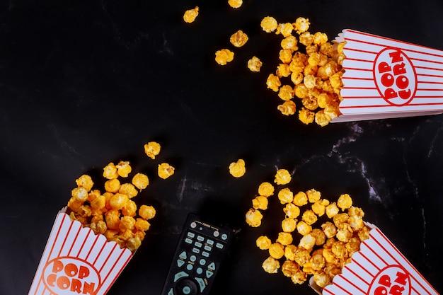Popcorn in gestreiften kisten auf schwarzer oberfläche mit fernbedienung verschüttet Premium Fotos