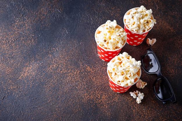 Popcorn mit gläsern 3d auf dunklem hintergrund Premium Fotos