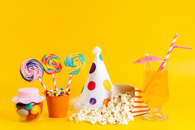 Popcorn und lutscher aus der vorderansicht sowie lustiger hut und cocktail auf gelb Kostenlose Fotos