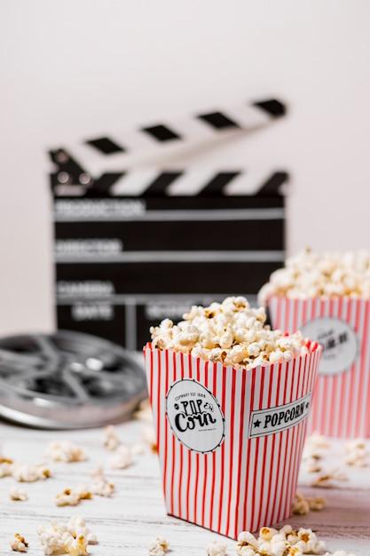 Popcornkästen mit filmrolle und clapperboard auf hölzernem schreibtisch Kostenlose Fotos