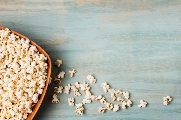 Popcorns liefen die schüssel auf blauem schreibtisch über Kostenlose Fotos
