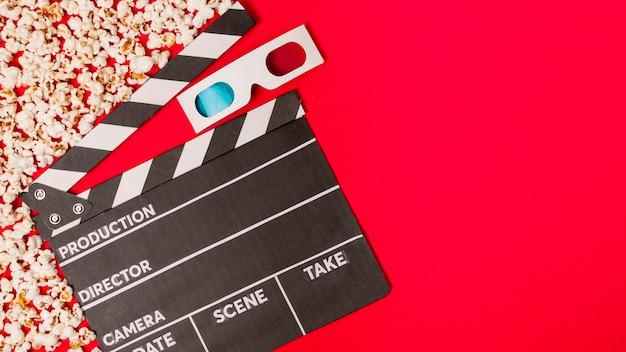 Popcorns mit clapperboard und gläsern 3d auf rotem hintergrund Kostenlose Fotos