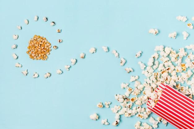 Popcornsamen mit gebogenen popcorns verschütteten vorderen kasten auf blauem hintergrund Kostenlose Fotos