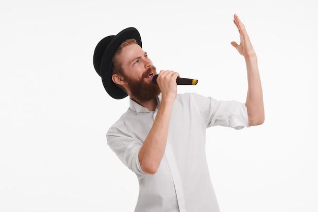 Popsänger mit fuzzy-bart, der emotional gestikuliert, während er mit dem mikrofon auftritt. attraktiver bärtiger junger männlicher animateur, der schwarzen hut und weißes hemd hält mikrofon hält und etwas ankündigt Kostenlose Fotos