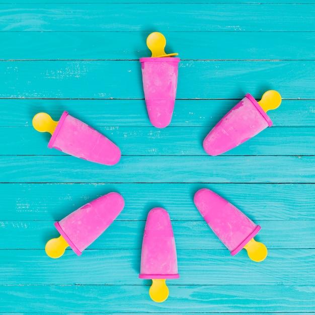 Popsicle hellrosa auf gelben essstäbchen auf türkistabelle Kostenlose Fotos