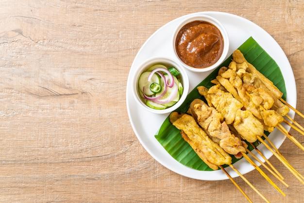 Pork satay - gegrilltes schweinefleisch, serviert mit erdnusssauce oder süß-saurer sauce Premium Fotos