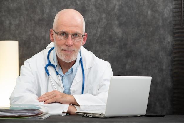 Porträt älteren doktors sitzend im ärztlichen dienst Premium Fotos