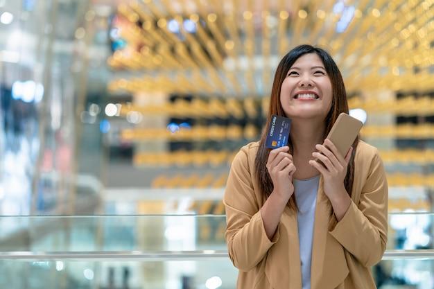 Porträt-asiatinglück, wenn kreditkarte und handy für das on-line-einkaufen im kaufhaus gehalten werden Premium Fotos