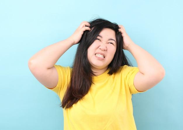 Porträt-asien-frauen glauben juckendem haar, auf einem blauen hintergrund im studio. Premium Fotos