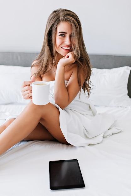 Porträt attraktives brünettes mädchen mit frechen beinen auf weißem bett in der modernen wohnung. sie hält lächelnd eine tasse in der hand. Kostenlose Fotos