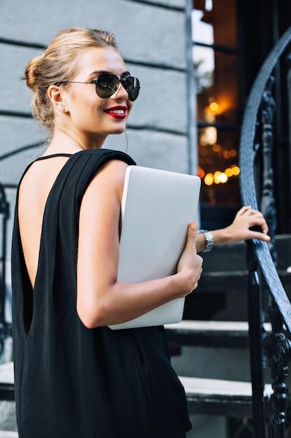Porträt attraktives modell im schwarzen kleid mit nacktem rücken auf treppen im freien. sie lächelt zur seite. Kostenlose Fotos