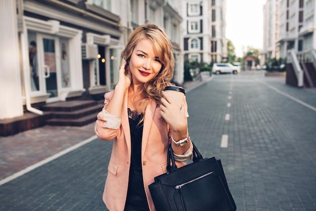 Porträt blondes modell mit langen haaren, die mit kaffee in der korallenjacke auf straße gehen. sie hat weinige lippen Kostenlose Fotos