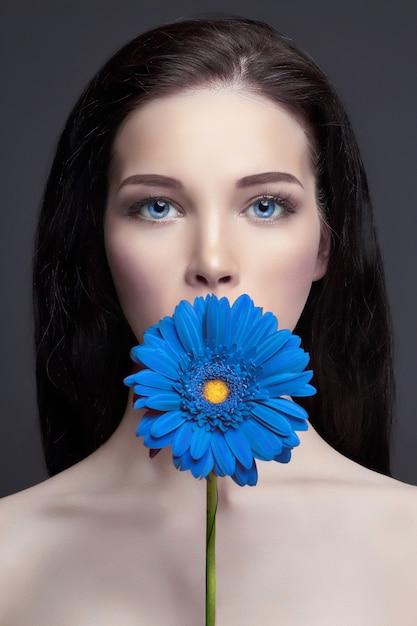 Porträt brunettefrau mit blauer blume in der hand Premium Fotos