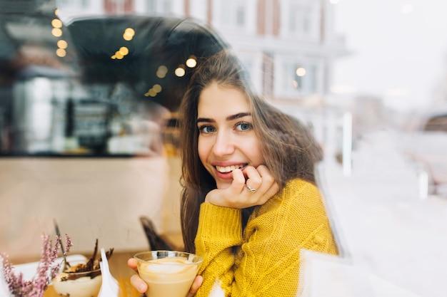 Porträt charmante junge frau mit freundlichem lächeln, lange brünette haare lächelnd im fenster des cafés in der winterzeit. wahre positive emotionen, freizeit, kaffee trinken, bei kaltem wetter chillen. Kostenlose Fotos