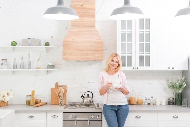 Porträt der älteren frau aufwerfend in der küche Kostenlose Fotos