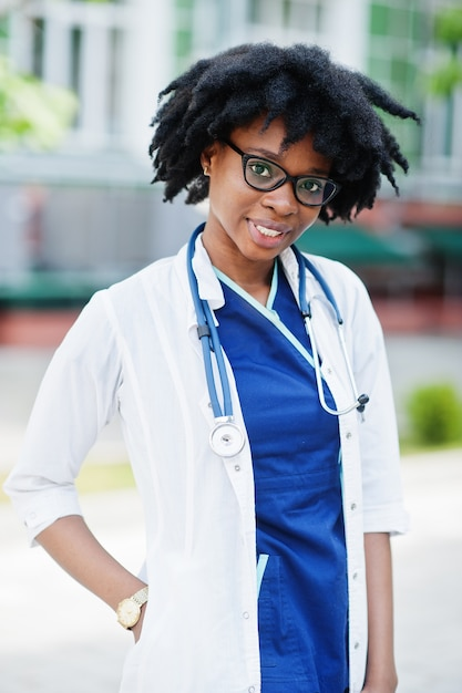 Porträt der afroamerikanischen ärztin mit stethoskop, das laborkittel trägt Premium Fotos