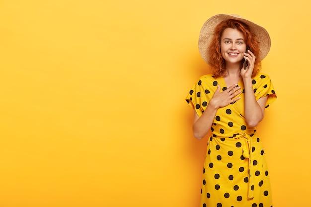 Porträt der angenehm aussehenden zufriedenen jungen rothaarigen frau hält handflächen auf der brust, fühlt sich beeindruckt, herzzerreißende geschichte über smartphone zu hören, trägt stilvolles leuchtend gelbes sommeroutfit Kostenlose Fotos