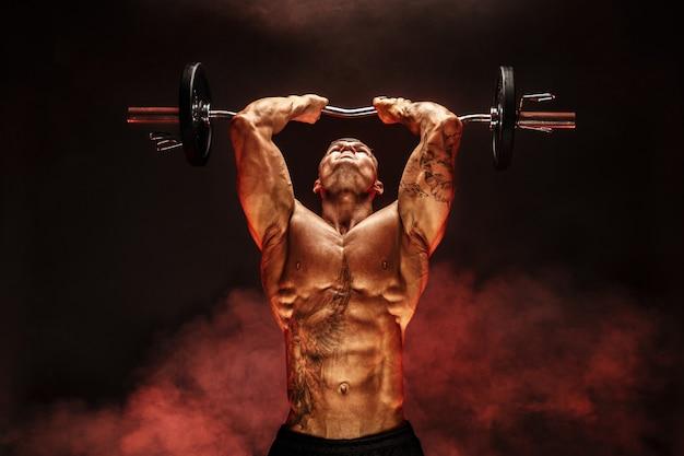 Porträt der anhebenden dummkopf des muskulösen mannes im roten rauch übung für trizeps-motivation Premium Fotos