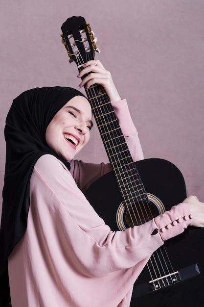 Porträt der arabischen frau mit gitarre Kostenlose Fotos