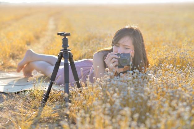 Porträt der asiatin eine kamera auf dem gebiet des trockenen grases halten. Premium Fotos