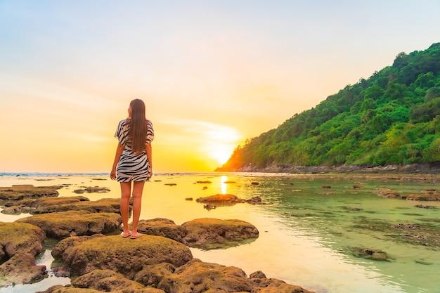 Porträt der asiatischen frau auf dem felsen bei sonnenuntergang um ozean im urlaub Kostenlose Fotos
