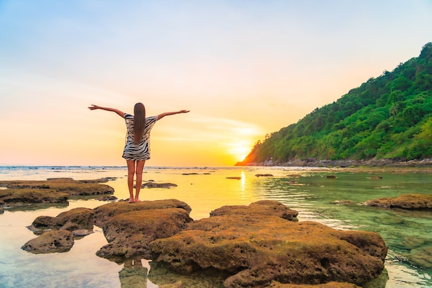 Porträt der asiatischen frau auf dem felsen mit geöffneten armen bei sonnenuntergang um ozean im urlaub Kostenlose Fotos