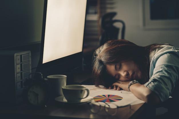 Porträt der asiatischen geschäftsfrau hart arbeiten und auf dem tisch schlafen Premium Fotos