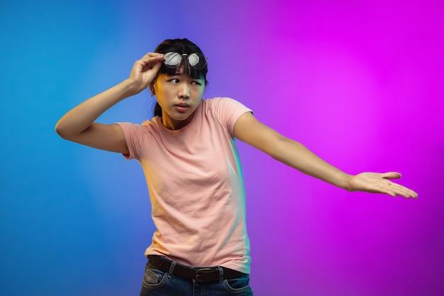 Porträt der asiatischen jungen frau auf gradientenstudiohintergrund in neon. schönes weibliches modell im lässigen stil. Kostenlose Fotos