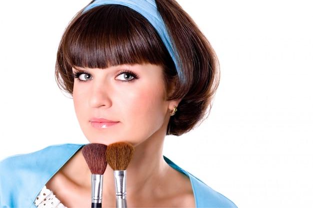 Porträt der attraktiven brunetfrau im blauen kleid mit zwei make-upbürsten lokalisiert auf weißem hintergrund Premium Fotos