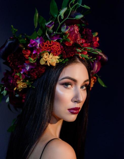 Porträt der attraktiven jungen frau mit hellem make-up gekleidet im großen bunten blumenkranz Kostenlose Fotos