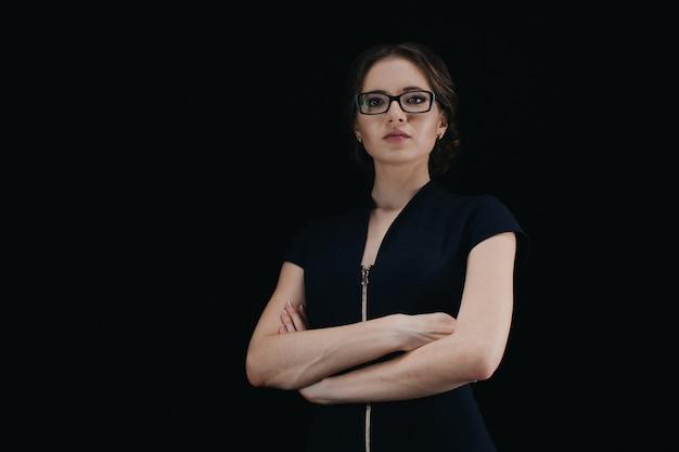 Porträt der attraktiven jungen kaukasischen geschäftsfrau mit den gekreuzten armen auf schwarzem Premium Fotos
