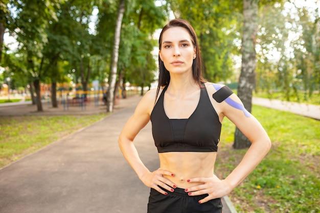 Porträt der attraktiven muskulösen brünetten frau, die schwarzes sportoutfit trägt und kamera betrachtet. junger lächelnder weiblicher athlet, der mit händen auf taille, buntes kinesiotaping auf körper aufwirft. Premium Fotos