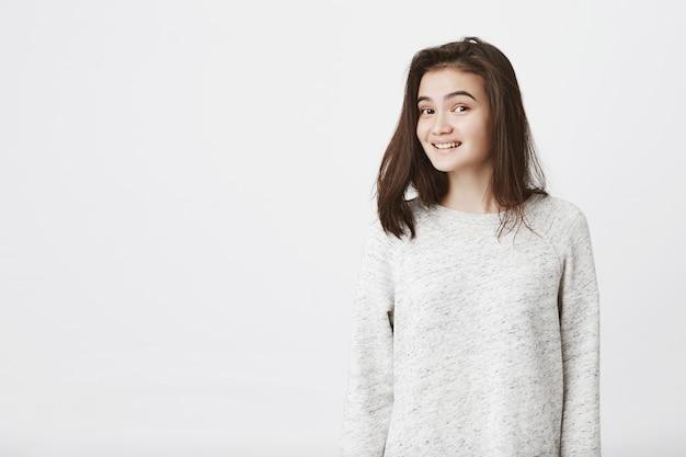 Porträt der attraktiven trendigen frau mit hochgezogenen augenbrauen, ängstlich lächelnd Kostenlose Fotos