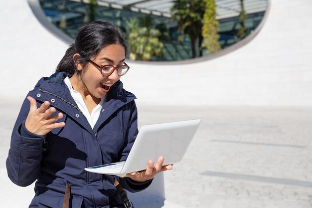 Porträt der aufgeregten jungen frau, die draußen laptop verwendet Kostenlose Fotos