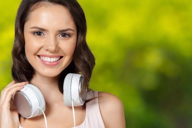 Porträt der brunetteschönheit hörend musik in den weißen kopfhörern Premium Fotos