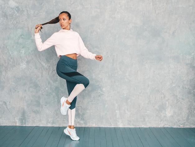 Porträt der eignungsfrau in der sportkleidung, die überzeugt schaut junge weibliche tragende sportkleidung schönes modell mit perfektem gebräuntem körper die frau springend in studio nahe grauer wand haarendstück der griffe in der hand Kostenlose Fotos