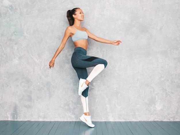 Porträt der eignungsfrau in der sportkleidung, die überzeugt schaut junge weibliche tragende sportkleidung schönes modell mit perfektem gebräuntem körper die frau springend in studio nahe grauer wand Kostenlose Fotos
