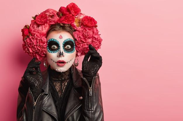 Porträt der emotionalen frau trägt professionelles zuckerschädel-make-up, hat angst gesichtsausdruck, hebt hand in schwarzen handschuhen mit entsetzen, bereitet sich auf halloween-urlaub Kostenlose Fotos