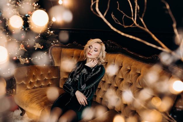 Porträt der entzückenden frau im schwarzen kleid, das in einer gemütlichen dunkelkammer mit weihnachtsdekor aufwirft Kostenlose Fotos
